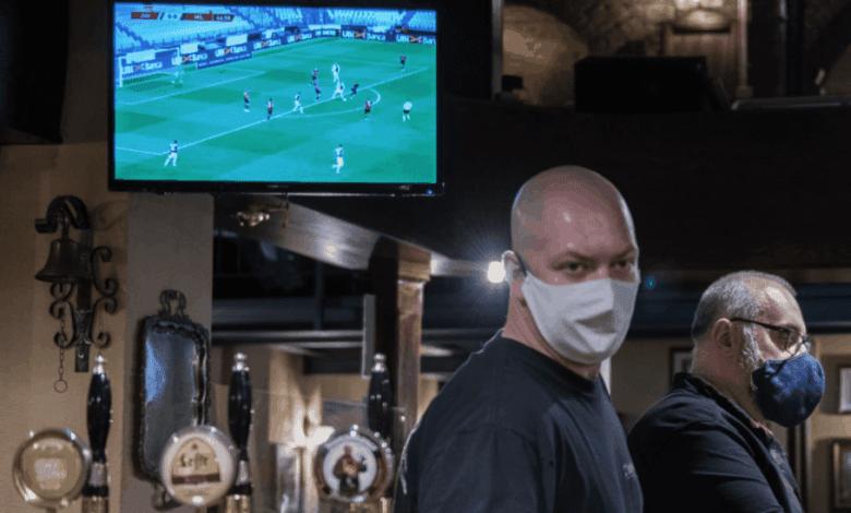 مقهى يعرض مباريات الدوري الايطالي، والعاملون يرتدون كمامات واقية من فيروس كورونا